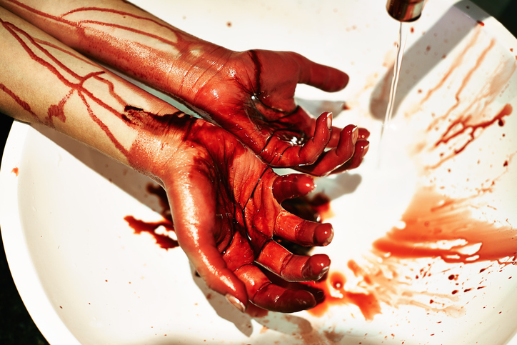 A cropped shot of a woman washing blood from her hands in a basin