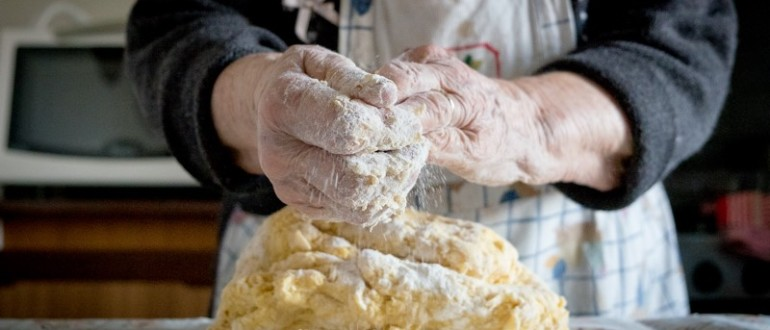 old woman making homemade fresh egg pasta with parmesan cheese in italian kitchen at home
